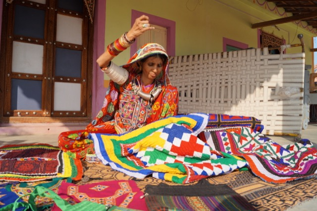 An Indian woman in a village hand-sewing with threads for Welspun's SPUN collection.