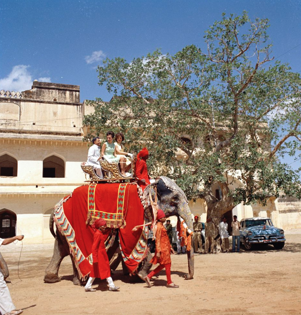 First Lady Jacqueline Kennedy rides an elephant during a trip to India