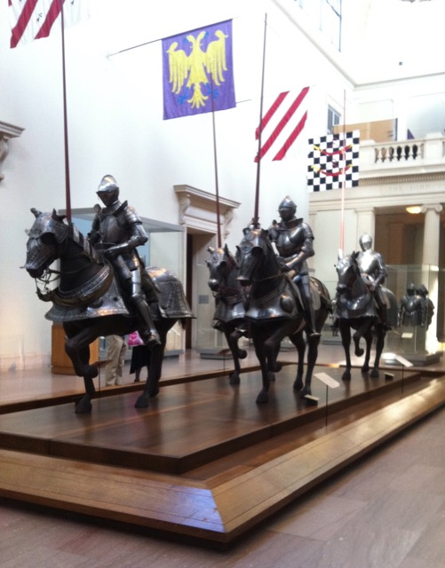 Chivalry expressed by armored horses and riders in The Emma and Georgina Bloomberg Arms and Armor Court at the MET.
