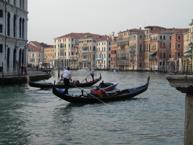 Gondoliers maneuver along the Grand Canal in Venice. Image © Saxon Henry.