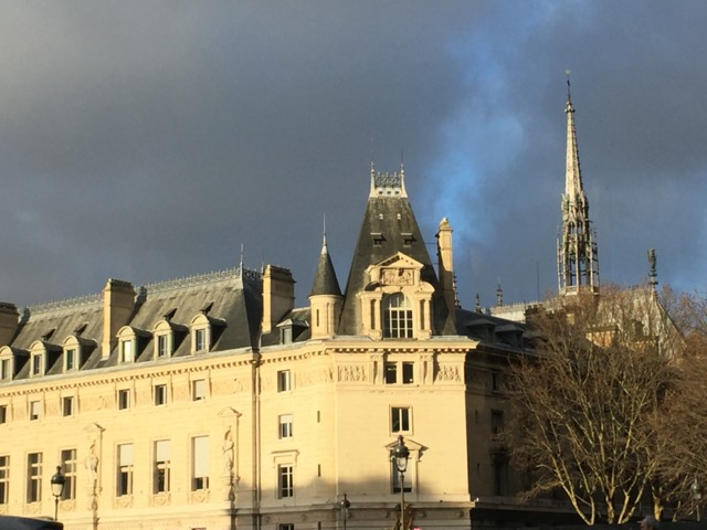The spire of Saint-Chapelle rises above the roof of the Conciergerie surrounding the river side of the Palais de la Cité complex, the photo taken from the Left Bank. Image © Saxon Henry.
