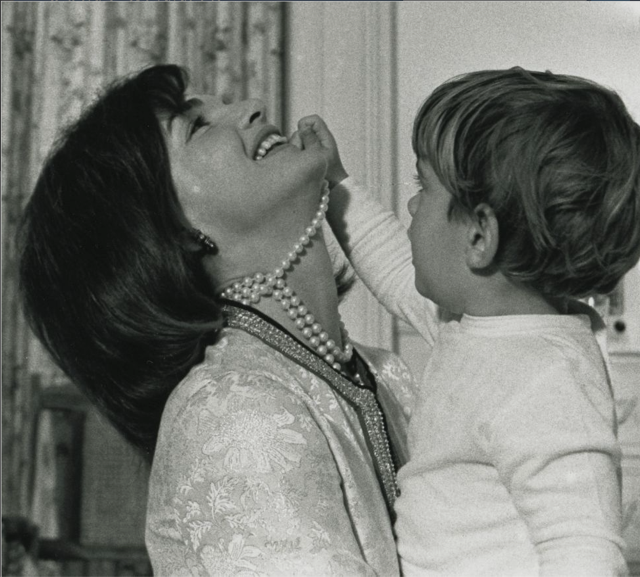John, Jr., playfully tugs at one of the three strands of Jackie's famous simulated pearl necklace