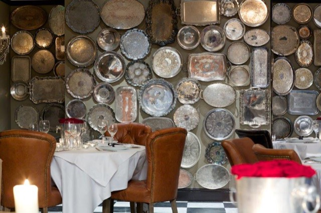 Silver platters in varying states of patina decorate a wall